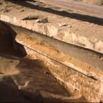 Z příkrovu písku se pomalu vynořuje stéla v podobě nepravých dveří (Intiho mastaba, Abúsír jih).